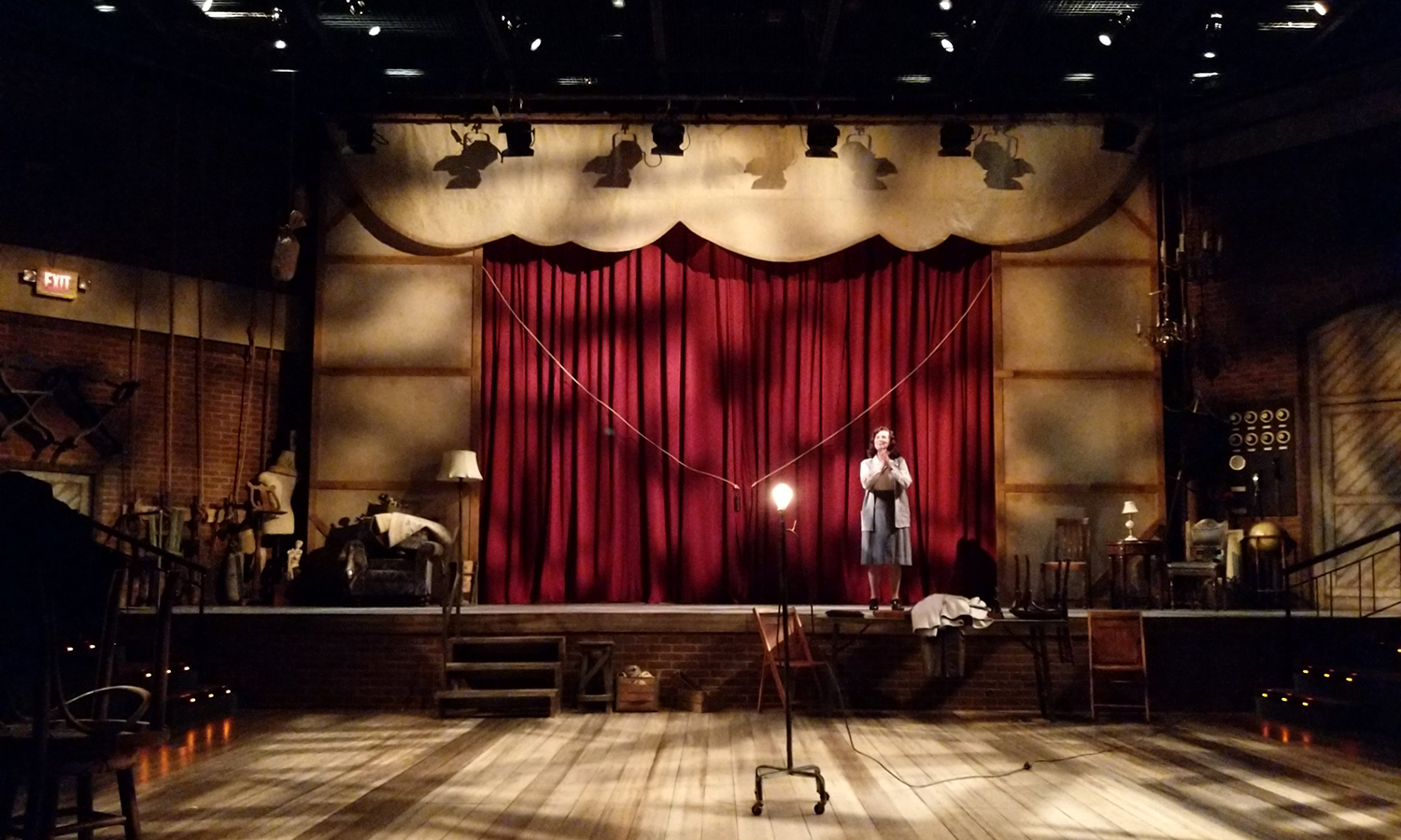 The backstage area of a theatre, with a red curtain on a raised platform. There are random props and items strewn about. A woman in a 1940s outfit is standing at stage left. Down on the lower level is a ghost light. The entire stage is covered in textured, selective lighting.