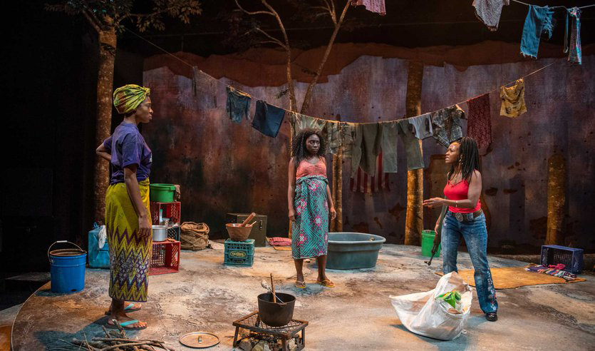 Three Black women are standing on a raised circular platform. The floor has sand and dirt on it, there are tree trunks upstage of the platform, with a wall further upstage. There is a clothesline with clothes hung on it. The wall is lit with texture, the trees are side light with warm light, and the warm light continues on the platform and the actors.
