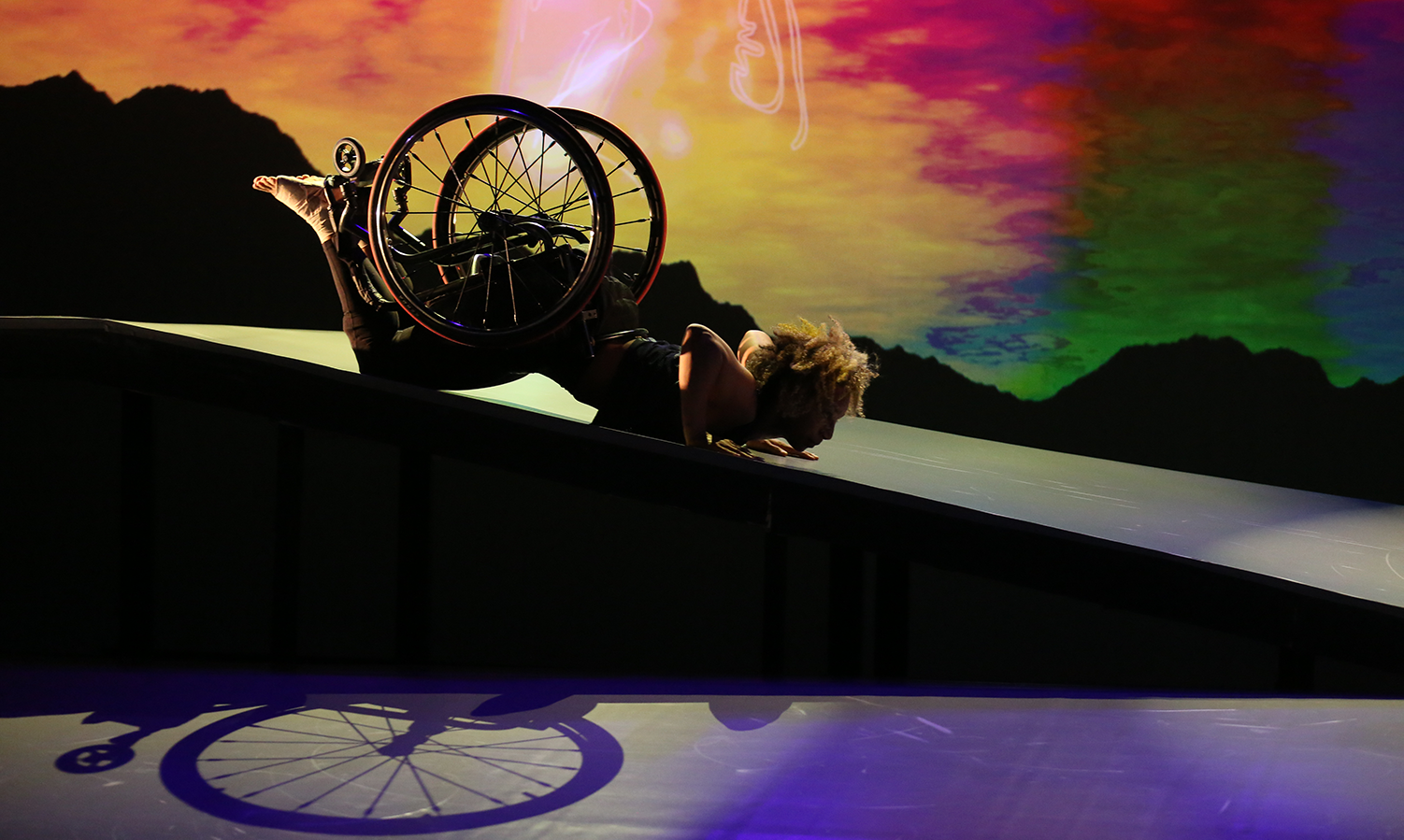 As the sky transitions from gold to amber to red, green and blue, Alice Sheppard, a light-skinned multiracial Black woman, slides in a spider position on her stomach down the shiny ramp. Her bent elbows, her wheelchair and the bottoms of her bare feet point upward as she stares down the Ramp. The shadow of her wheelchair is visible beneath her short curly hair glows in the light.