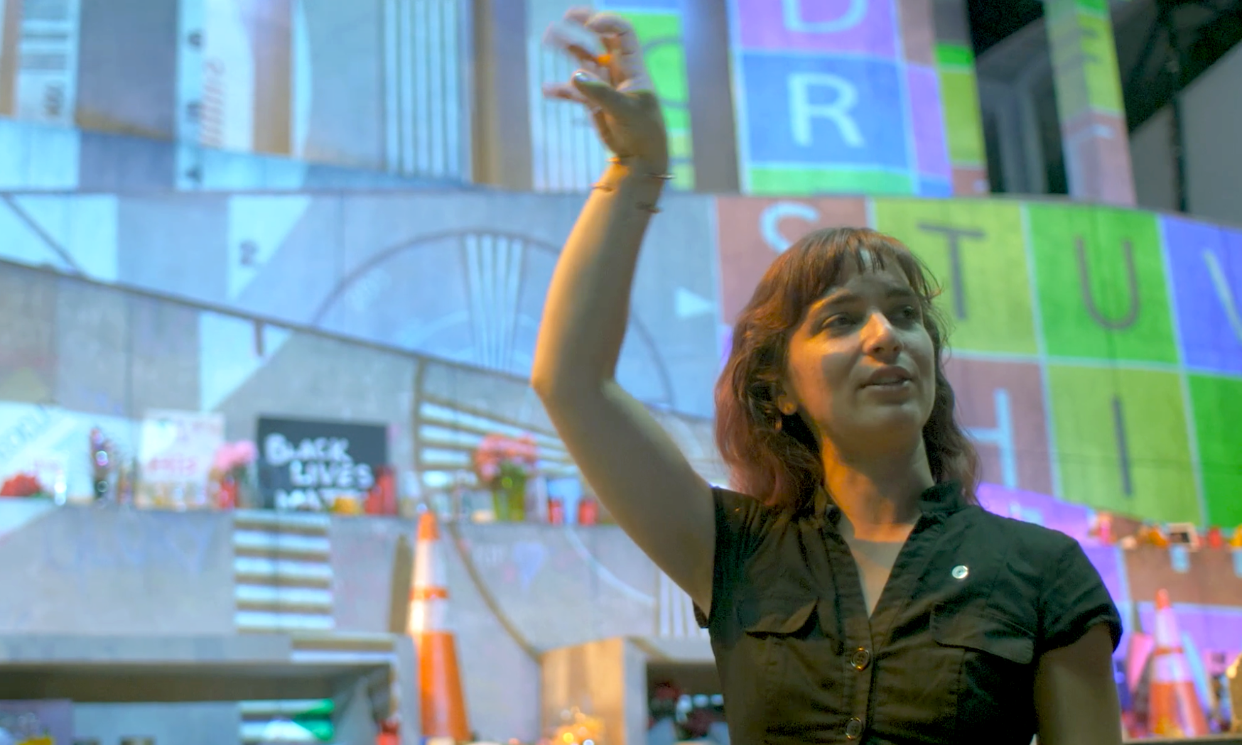 Katherine Freer, a white woman with long brown hair wearing a black dress, gestures at the slightly out of focus stage for a production of Antigone, where the architecture is illuminated by the projections of a colorful focus grid.
