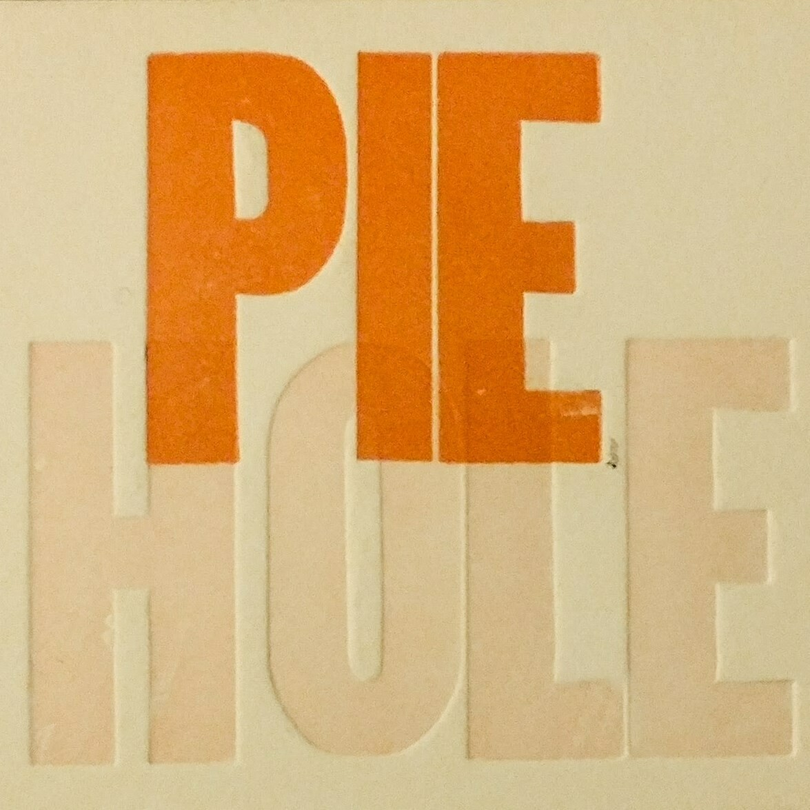 orange and tan text PIE HOLE over tan background.