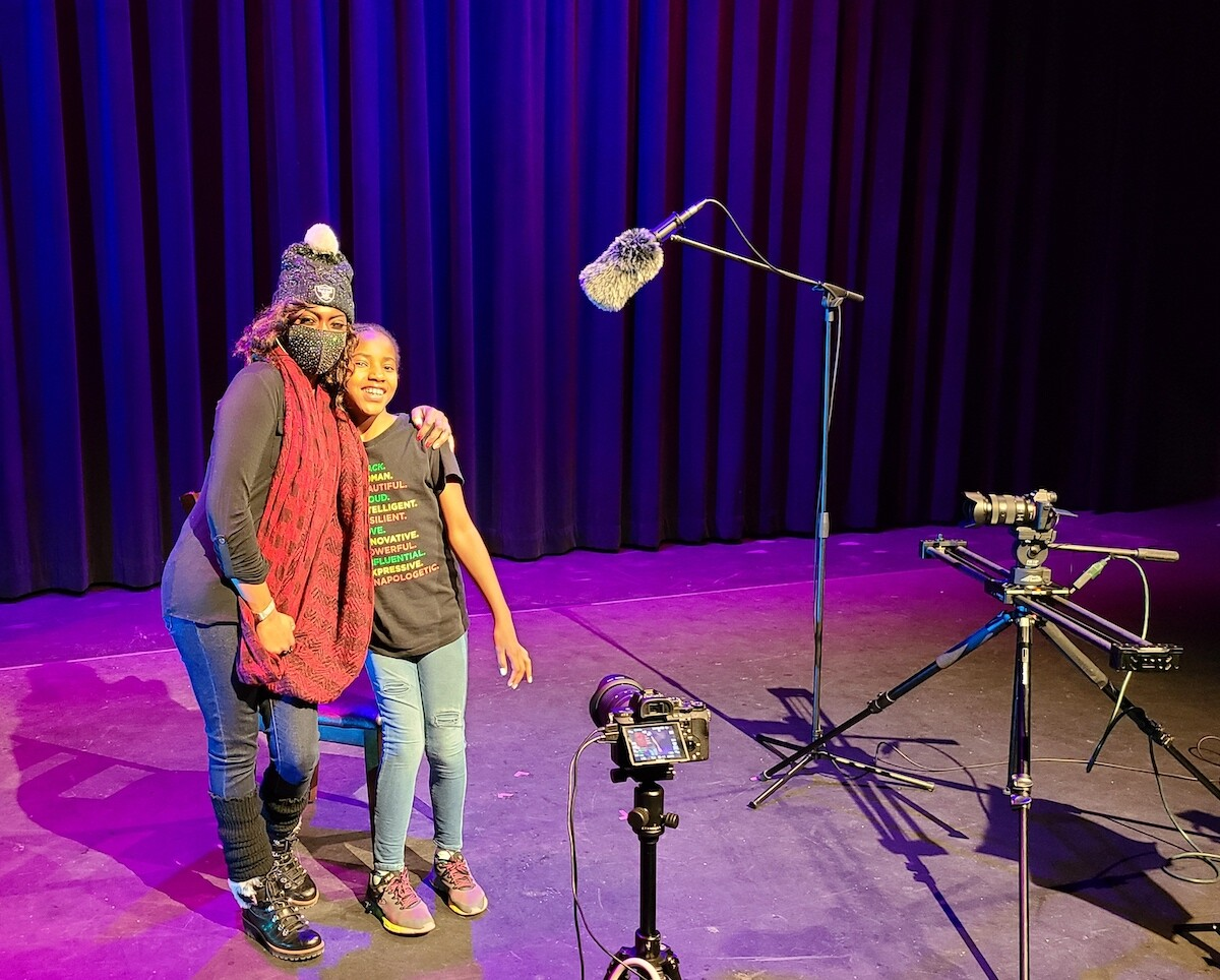Image of an adult and child standing on a stage with recording equipment.