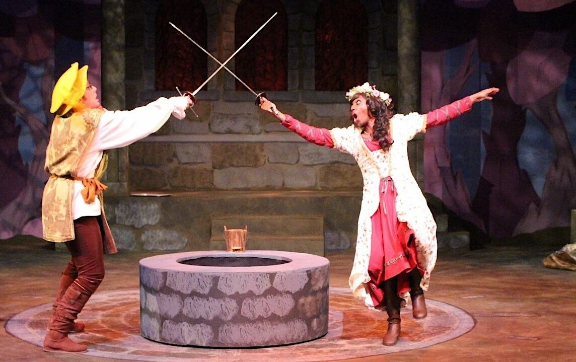 An image of two actors dressed in medieval period clothing having a sword fight.