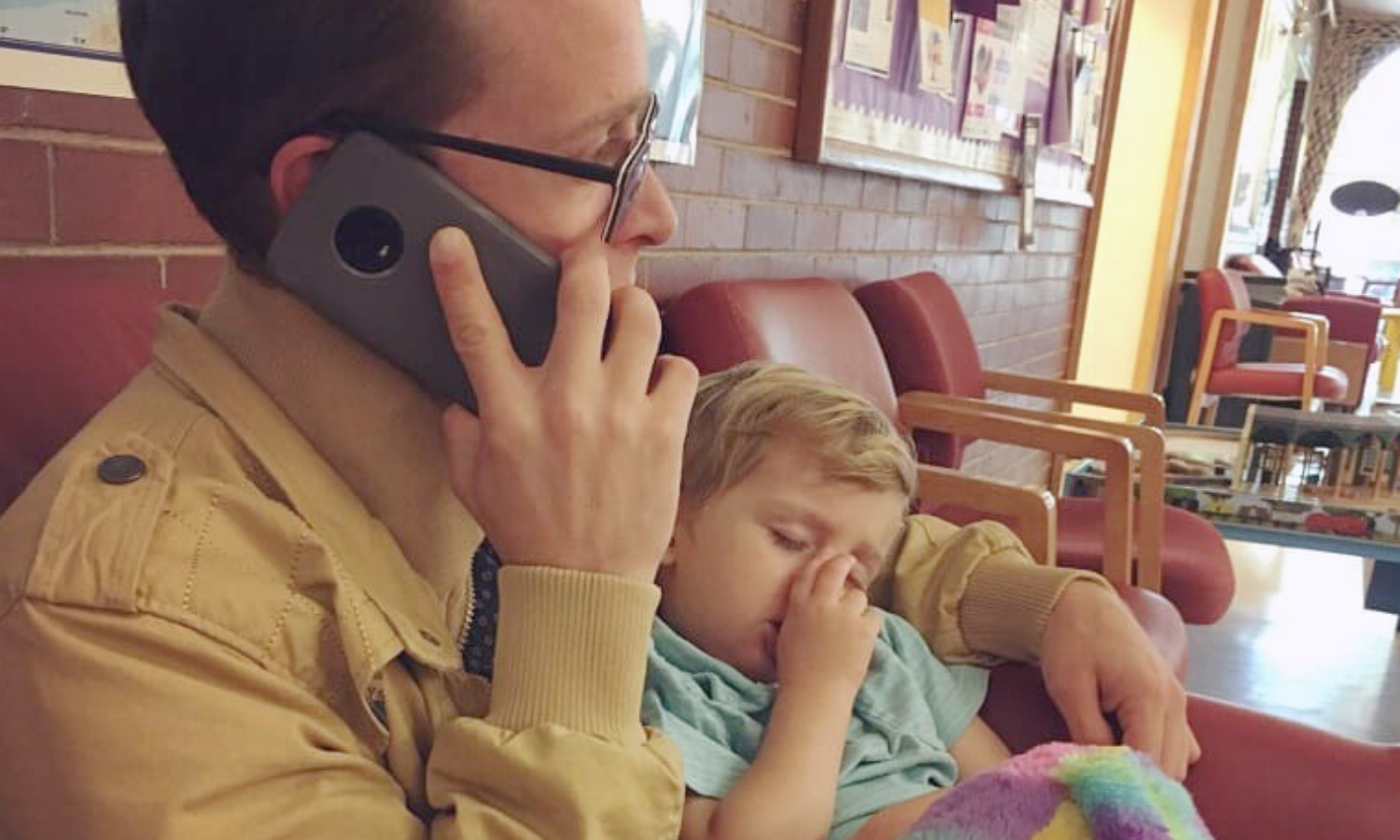 A man is sitting holding a phone up to his ear while a toddler sleeps on him. The toddler is holding a rainbow colored stuffed animal.