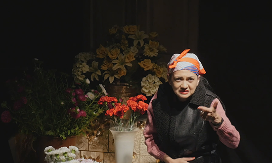 An elderly woman in front of flowers.