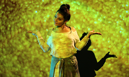 A teenage girl in front of abstract video projections.