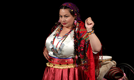 Roma woman in traditional clothes on stage.