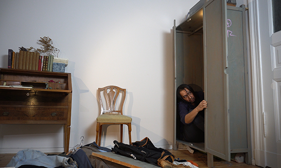A man peaking out of a cabinet in a apartment room.