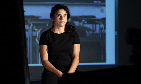 woman in black t-shirt in front of a video projection of a classroom.