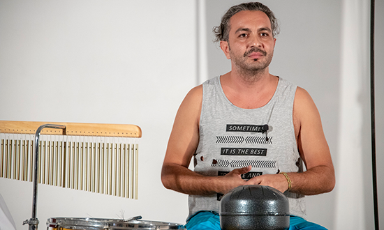 a man in a grey tank top in front of percussion instuments.