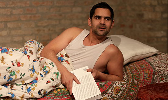 a man in an undershirt sitting up in bed holding a book.