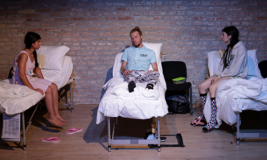 Three performers lying in hospital beds.