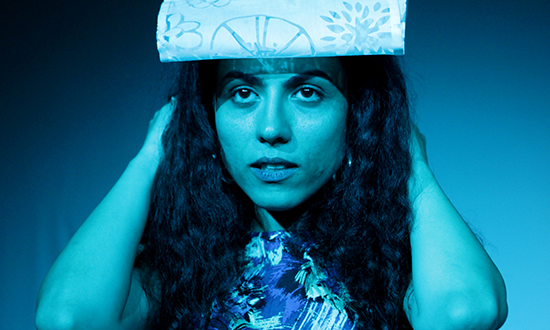 a women holding a folded paper on her head.
