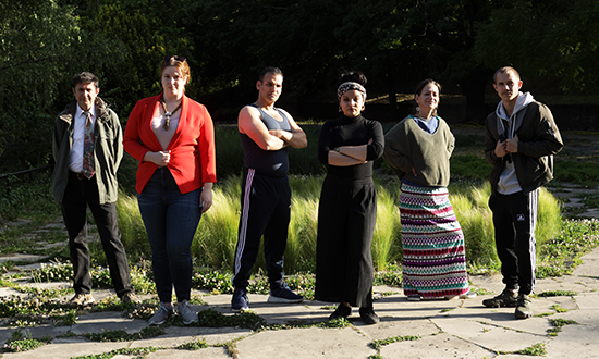 Six performers posing for a picture in a park.