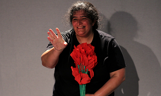A woman holding a bouquet of red flowers.