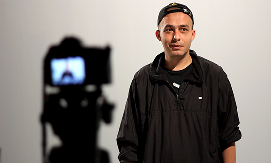 A man in backwards baseball cap stands in front a camera tripod.